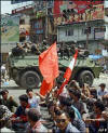 A Nepalese Army armoured vehicle passes by protestors staging a sit-in protest rally on the 16th day of a general strike at Kalanki in Kathmandu